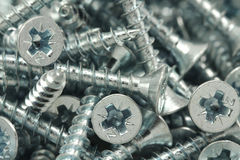 A handful of shiny anodized screws royalty free stock photography