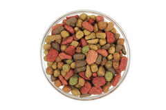 A handful of small granules pet food in a glass cup Royalty Free Stock Photo
