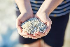 Handful of small white pebbles from. Girl with handful of small white pebbles from `rice beach` Is Arutas in Sardinia, Italy royalty free stock photography