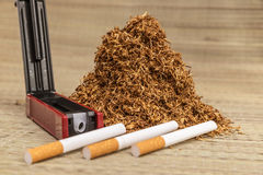 Handful of smoking tobacco. Surrounded by a cigarette manufacturing accessories stock image