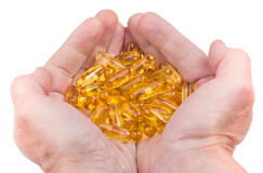 Handful of softgels fish oil in male hands Stock Photo