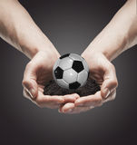 A handful soil with classic soccer ball in the man Royalty Free Stock Image
