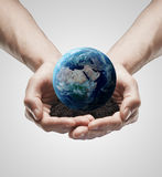 Handful soil with the Earth in the male hands Stock Images