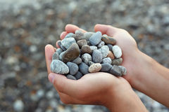 Handful of stones in hands, Against stones Royalty Free Stock Photo