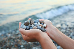 Handful of stones in hands, Against stones and sea Stock Photo