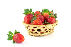 Handful of strawberries in a wicker basket. On a white background Stock Photos