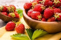 A handful of strawberries in a wooden plate, napkin and leaves Stock Photos