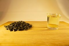A handful of sunflower seed, sunflower oil in a glass on the table. Side view royalty free stock image