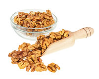 Handful of walnuts in scoop and glass bowl isolated on white. Royalty Free Stock Photos