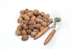 Handful of walnuts on white background, with a nutcracker Royalty Free Stock Images
