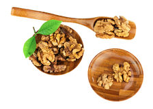 Handful of walnuts in wooden bowls, scoop and green leaves isola Stock Images