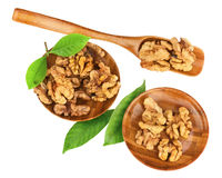 Handful of walnuts in wooden bowls, scoop and green leaves. Stock Photo
