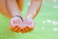 Handful and Water. Woman's hands playing with fresh water Royalty Free Stock Images
