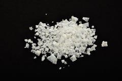 Handful of white Cyprian pyramid sea salt  on black Stock Image