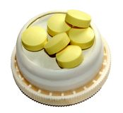 Handful of yellow pills. On a lid Royalty Free Stock Photos