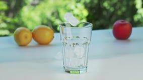 Handfulliskuber som kastar i tomt exponeringsglas, nära skott Gula citroner, rött äpple och exponeringsglas på vit yttersida Gr?s lager videofilmer