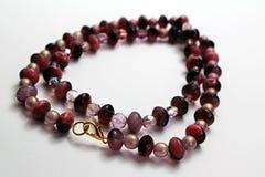 Handgefertigte Halskette gemacht von den roten und rosa Glasedelsteinen, von den Perlen und vom silbernen Schmuckdraht Stockbild