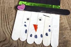Handgefertigter Eis am Stiel-Schneemann, der auf einen hölzernen Kornhintergrund legt Lizenzfreie Stockbilder