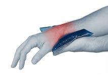 Handgelenkschmerz. Mann, der Eisbeutel auf Handgelenk hält. Lizenzfreies Stockfoto