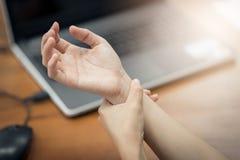 Handgelenkschmerz von der Anwendung des Computers Stockfoto