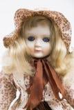Handgemachte blonde Puppe des keramischen Porzellans mit Textilhut und braunem Kleid Stockfotografie