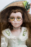 Handgemachte blonde Puppe des keramischen Porzellans mit Weidenhut und gelben Gläsern Lizenzfreies Stockfoto