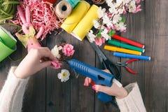Handgemachte Blumen des Frauenklebers mit Schmelzgewehr stockbilder