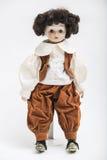 Handgemachte Puppe des keramischen Porzellans eines Brunettejungen im braunen Kostüm Lizenzfreies Stockbild