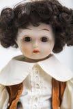 Handgemachte Puppe des keramischen Porzellans eines Brunettejungen im braunen Kostüm Stockbilder
