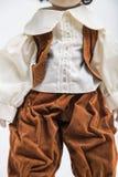 Handgemachte Puppe des keramischen Porzellans eines Brunettejungen im braunen Kostüm Stockbild