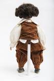 Handgemachte Puppe des keramischen Porzellans eines Brunettejungen im braunen Kostüm Lizenzfreies Stockfoto