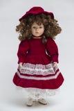 Handgemachte Puppe des keramischen Porzellans mit dem gelockten braunen Haar und rotem Kleid Stockfoto
