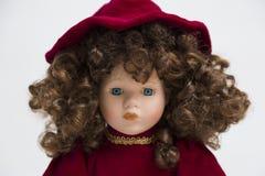 Handgemachte Puppe des keramischen Porzellans mit dem gelockten braunen Haar und rotem Kleid Stockfotos