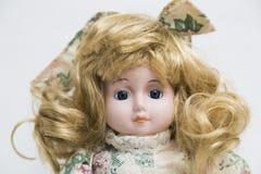 Handgemachte Puppe des keramischen Porzellans mit dem langen blonden Haar und Blumenkleid Stockfotos