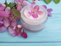 Handgemachte rosa Blumen der kosmetischen Lotionssalbenentspannungsfeuchtigkeitscremeschutzglaswesentlich-Sahnemagnolie auf blaue lizenzfreies stockfoto
