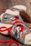Handgemachte rustikale Socken mit einem Wintermuster auf dem hölzernen Hintergrund, Kiefernkegel Kopieren Sie Raum für Ihren Text Stockbild