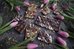 Handgemachte Schokolade mit Nüssen und Trockenfrüchten mit rosa Tulpen, Chocolatier, süße Geschenke, Valentinstag, weißer Tag, Ho stockbild