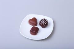 Handgemachte Schokoladenpralinen der Zartheit auf weißer Untertasse Stockfoto