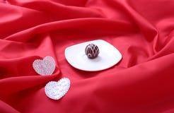 Handgemachte Schokoladenpralinen der Zartheit und Dekorationsherz auf weißer Untertasse Stockbild