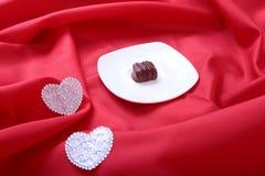 Handgemachte Schokoladenpralinen der Zartheit und Dekorationsherz auf weißer Untertasse Lizenzfreie Stockfotografie
