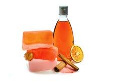 Handgemachte Seife, orangefarbene Duschgelflasche und Zimt Stockfotos