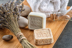Handgemachte Seifen mit Lavendelbündel und -steinen auf hölzernem Brett, Produkt von Kosmetik oder Körperpflege stockfotos