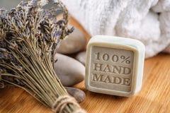 Handgemachte Seifen mit Lavendelbündel und -steinen auf hölzernem Brett, Produkt von Kosmetik oder Körperpflege Stockbild
