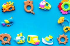 Handgemachte Spielwaren für neugeborenes Babyjungen-, Plastik- und hölzernesgeklapper auf blauem Draufsichtraum des Hintergrundes lizenzfreies stockbild