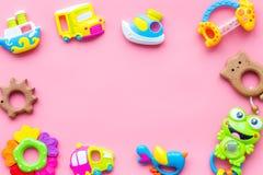 Handgemachte Spielwaren für neugeborenes Babymädchen-, Plastik- und hölzernesgeklapper auf Draufsicht-Kopienraumfachwerk des Rosa lizenzfreie stockfotos
