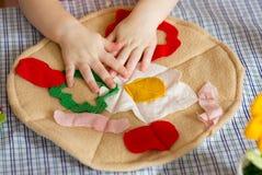 Handgemachte Textilspielzeugpizza und -Kinderhände Stockfotografie