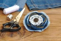 Handgemachter Denimblumenschmuck Scheren, Thread, Muffe, Nadel, weibliche alte Jeans auf einem hölzernen Hintergrund Stockbilder