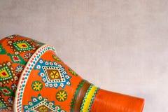 Handgemachter künstlerischer geschmerzter orange Tonwarenvase über Schmutzbeschaffenheit lizenzfreies stockfoto