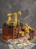Handgemachter Kuchen mit schwarzer Schokoladenglasur, -Erdölbohrturm und -dollar auf einem dunkelgrauen konkreten Hintergrund Stockfotos