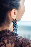 Handgemachter Ohrring auf dem Ohr einer jungen Frau stockfotos